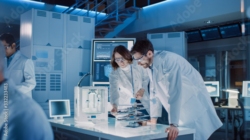 Obraz Diverse International Team of Industrial Scientists and Engineers Wearing White Coats Working on Heavy Machinery Design in Research Laboratory. Professionals Using 3D Printer, Computers and Microscope - fototapety do salonu