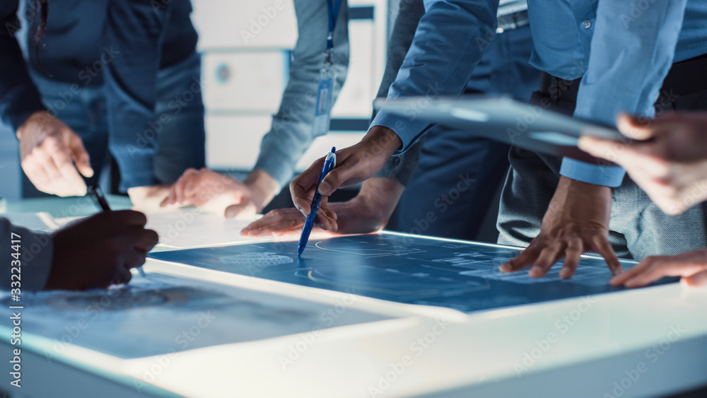 Fototapeta Engineer, Scientists and Developers Gathered Around Illuminated Conference Table in Technology Research Center, Talking, Finding Solution and Analysing Industrial Engine Design. Close-up Hands Shot