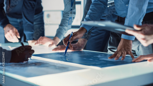 Engineer, Scientists and Developers Gathered Around Illuminated Conference Table in Technology Research Center, Talking, Finding Solution and Analysing Industrial Engine Design. Close-up Hands Shot