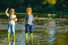 Skipping Stones On Water. Children In Action Of Throwing Stone Or Rock In Water.