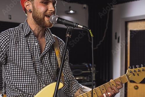 Photo professional caucasian singer play electric guitar in recording studio
