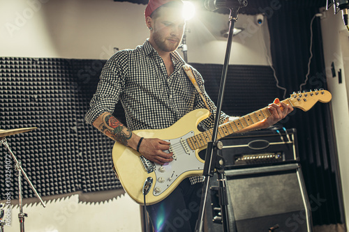 awesome caucasian musician play electric guitar and sing in recording studio Wallpaper Mural