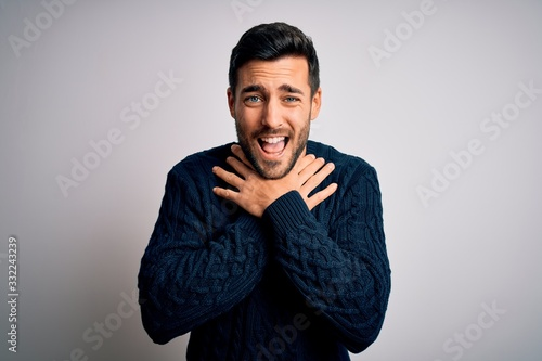 Photo Young handsome man with beard wearing casual sweater standing over white background shouting and suffocate because painful strangle