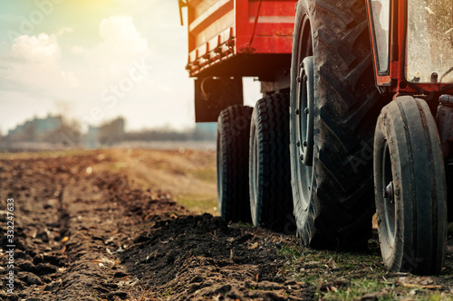 Photo Old red agricultural tractor with trailer on dirt countryside road