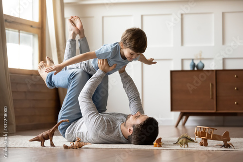 Carta da parati Happy young father lying on floor in living room hold fly with little preschoole