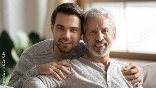 Portrait of smiling elderly father posing looking at camera hugging with adult g Canvas Print