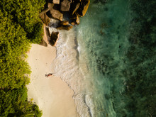 Tropical Beach, Coral Sand, Green Vegetation, Large Rocks, Waving Ocean, Splashes, And A Red Swisuit Sexy Woman From High Above, Birds Eye View.