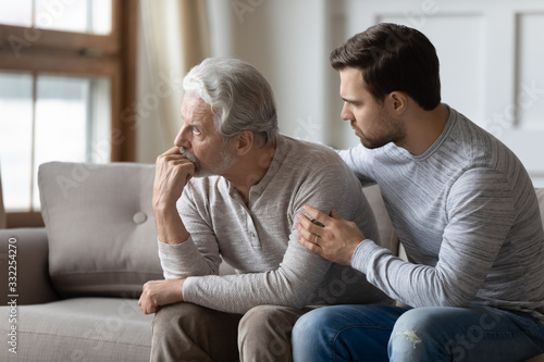 Loving young man embrace comfort upset elderly gray-haired dad suffering from de Wallpaper Mural