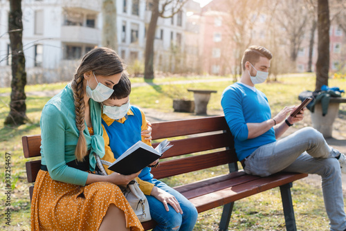 Photo People sitting on park bench in the sun practicing social distancing