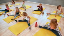 Flexible Kids. Group Of Children Sitting On The Floor And Doing Gymnastic Exercises In The Dance Studio. Physical Education