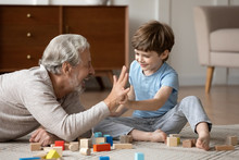 Overjoyed Senior Grandfather Lying On Floor In Living Room Play With Blocks With Cute Little Grandson, Happy Mature Grandparent Relax Engaged In Game With Building Bricks With Small Grandchild At Home