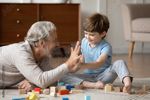 Obraz Overjoyed senior grandfather lying on floor in living room play with blocks with cute little grandson, happy mature grandparent relax engaged in game with building bricks with small grandchild at home - fototapety do salonu