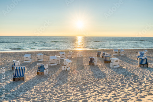 Fotografie, Obraz Roofed wicker beach chairs at the North Sea coast on Sylt, Germany