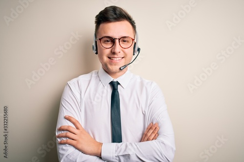 Young handsome caucasian business man wearing call center headset at customer service happy face smiling with crossed arms looking at the camera Fototapete