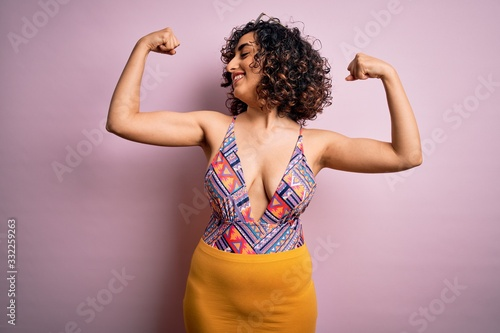Fotografija Young beautiful arab woman on vacation wearing swimsuit and sunglasses over pink background showing arms muscles smiling proud