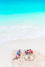 Father And Little Daughters Making Sand Castle At Tropical Beach