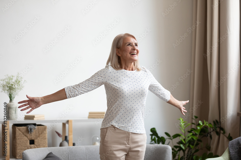 Fototapeta Overjoyed mature grandmother standing with outstretched arms near comfortable couch, breathing fresh air, enjoying freedom, happy life moment. Smiling older woman feeling thankful for good day.