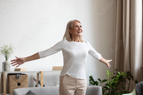 Obraz Overjoyed mature grandmother standing with outstretched arms near comfortable couch, breathing fresh air, enjoying freedom, happy life moment. Smiling older woman feeling thankful for good day. - fototapety do salonu