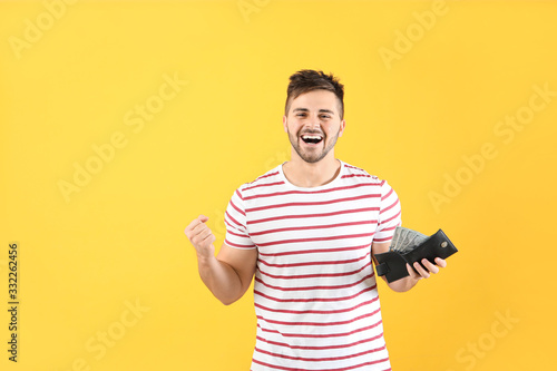 Fototapeta Happy man with purse on color background obraz