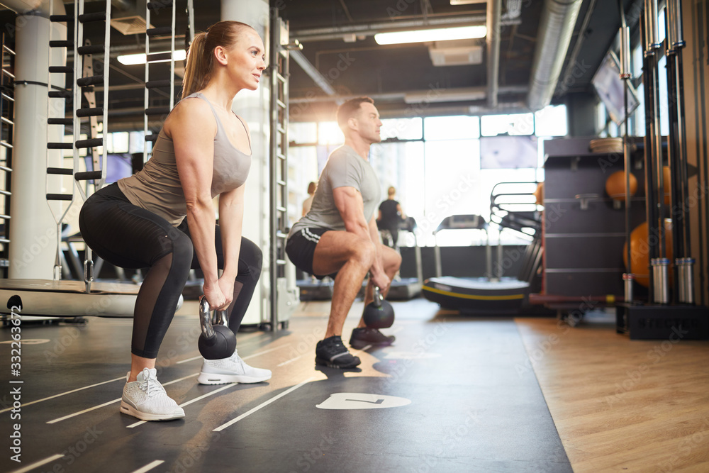 Fototapeta Full length side view portrait of muscular couple swinging kettlebells during strength workout in modern gym, copy space