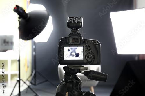 Obraz Professional camera on tripod in modern photo studio - fototapety do salonu