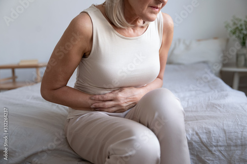 Vászonkép Cropped image older unhealthy woman embracing belly, suffering from strong stomach ache