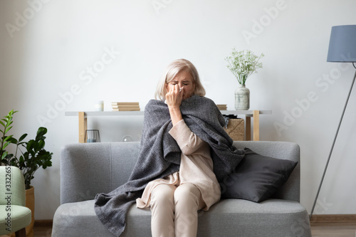 Fotografia, Obraz Unhealthy middle aged woman covered in blanket sitting on sofa in living room