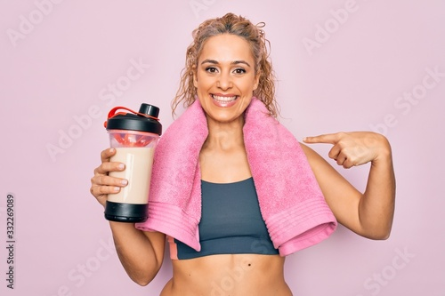 Fotografia Beautiful blonde sporty woman doing sport wearing towel holding shaker with prot