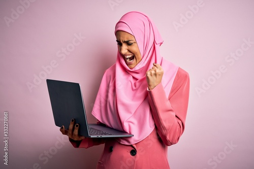Young beautiful businesswoman wearing pink muslim hijab and business jacket usin Canvas Print