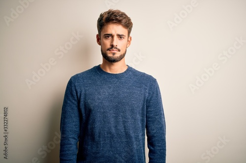 Young handsome man with beard wearing casual sweater standing over white background Relaxed with serious expression on face Fototapete