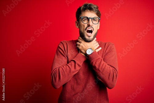 Photo Young handsome man with beard wearing glasses and sweater standing over red background shouting suffocate because painful strangle