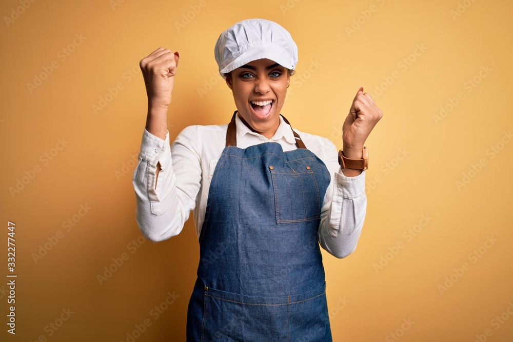 Fototapeta Young african american afro baker woman wearing apron and cap over yellow background celebrating surprised and amazed for success with arms raised and open eyes. Winner concept.