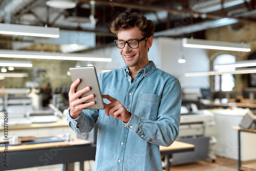 Work and have fun. Young businessman posing in office