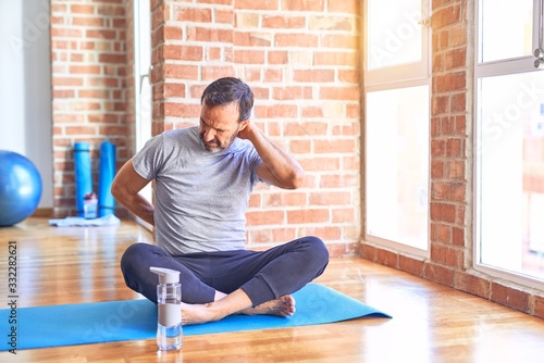 Middle age handsome sportman sitting on mat doing stretching yoga exercise at gy Fototapeta