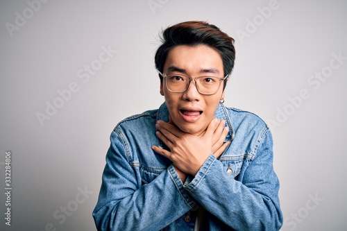 Young handsome chinese man wearing denim jacket and glasses over white background shouting and suffocate because painful strangle Wallpaper Mural