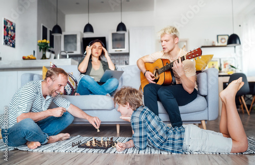 Fototapeta Family at living room together. Father playing chess with little son, mother learning online using laptop, older son playing acoustic guitar and singing a songs. Quarantine time and family concept. obraz