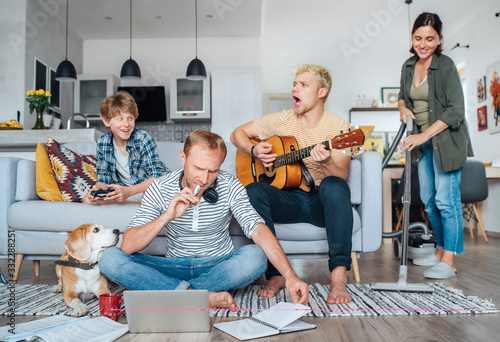 Obraz Quarantine time: Family at living room together. Father distance working using laptop, mother cleaning the room, older son playing acoustic guitar and singing a songs, little son playing video console - fototapety do salonu