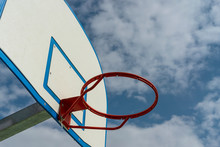 Close-up Photograph Of The Basketball Backboard And Hoop. The Court Is On The Street.