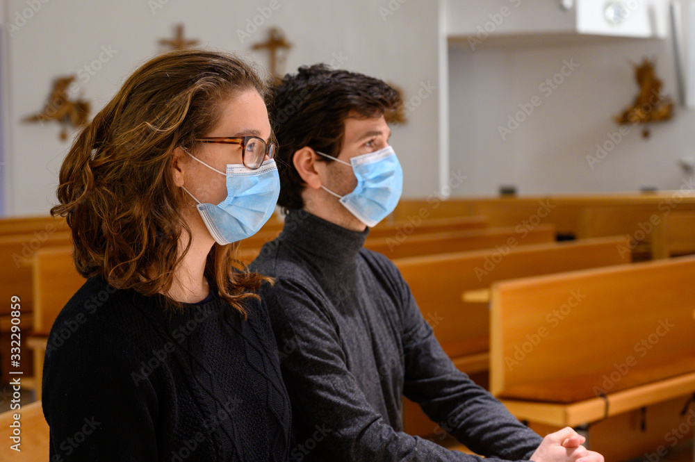 Fototapeta A young couple in face masks praying in a church during the COVID-19 pandemic. Bratislava, Slovakia.