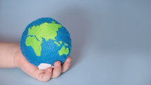 Small Child Holds Earth. Palm Of Child With Thimble Of Felt In Form Of Planet. Saving Ecology With Children. Cosept Earth Day.World Ocean Day, Saving Water Campaign