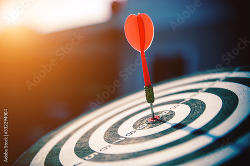 Photo Bullseye(bull's-eye) or dart board has dart arrow hitting the center of a shooting target for business targeting and good success