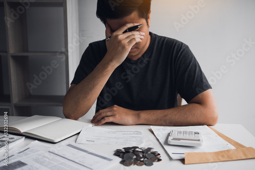 Obraz na płótnie Asian men are stressed about financial problems, with invoices and calculators placed on the table while having stress on problems with home expenses