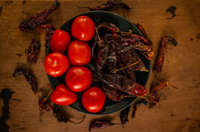 Still Life Photograph With Tomatoes, Pasilla Peppers And Dried Chilacas, On A Rustic Table, Ingredients Used In Traditional Mexican Cuisine