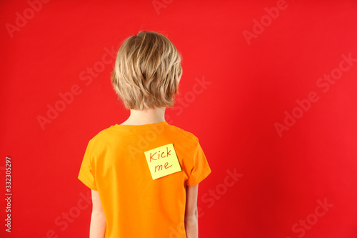 Little boy with KICK ME sticker on back against red background, space for text. April fool's day