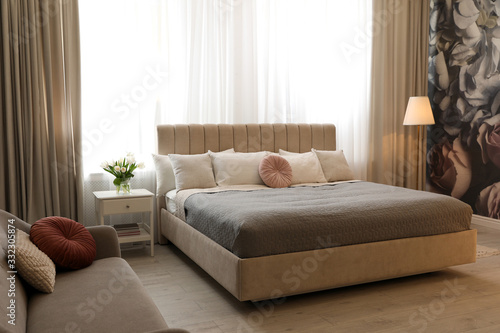 Beautiful room interior with large comfortable bed Wallpaper Mural