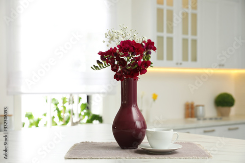 Obraz Beautiful bouquet with freesia flowers and cup on table in kitchen - fototapety do salonu