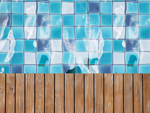 Background Of Rippling Water Surface Over Blue Tiled At Bottom Of Swimming Pool.
