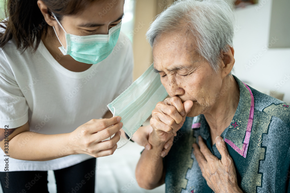Fototapeta Old people have illness,fever,cough and difficulty breathing,infectious symptoms of flu,pandemic of Covid-19,asian caregiver wearing a mask to sick senior woman,prevent outbreak,spread of Coronavirus