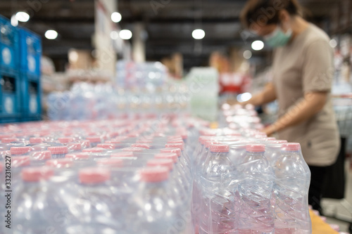 Fotografía Lot of plastic packaging of fresh water,people wearing face mask,choosing fresh