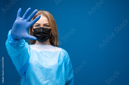 Obraz Stock photo portrait of a Caucasian adult woman in black respiratory mask, blue robe and rubber glove showing stop gesture at camera with her hand. Stop coronavirus concept. Copy space. - fototapety do salonu